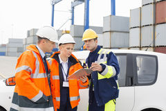 Workers discussing over clipboard beside car in shipping yard Stock Photography