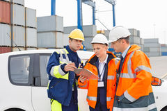 Workers discussing over clipboard beside car in shipping yard royalty free stock image