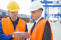 Workers discussing over clipboard in shipping yard Royalty Free Stock Image