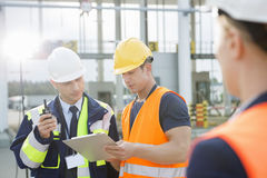 Workers discussing over clipboard in shipping yard Royalty Free Stock Photo