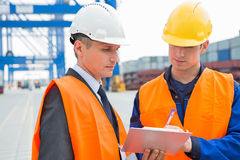 Workers discussing over clipboard in shipping yard Stock Photos