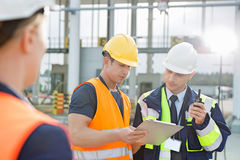 Workers discussing over clipboard in shipping yard Stock Images