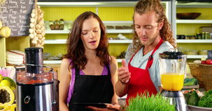Workers discussing over digital tablet at juice counter. In organic market stock video footage