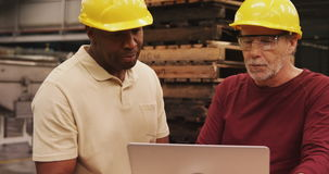Workers discussing over laptop stock video footage