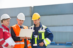 Workers discussing over laptop in shipping yard Royalty Free Stock Images