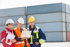 Workers discussing over laptop in shipping yard Stock Image