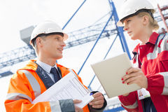 Workers discussing over tablet computer in shipping yard royalty free stock photography