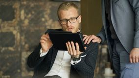 Workers discussing project with tablet in cafe during business lunch. Blond man with beard in white shirt, black jacket. Workers discussing project with tablet stock footage