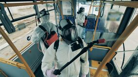 Workers disinfect one bus during covid-19 pandemic.