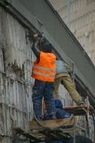 Workers dismount wall cladding royalty free stock photos