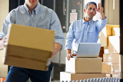 Workers In Distribution Warehouse. Packing stock photos
