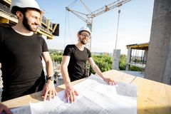 Workers with drawings at the construction site. Two workers in black t-shirts and protective harhats working with drawings at the construction site outdoors stock photo