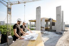 Workers with drawings at the construction site. Two workers in black t-shirts and protective harhats working with drawings at the construction site outdoors stock photos