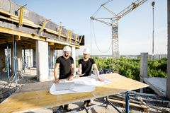 Workers with drawings at the construction site. Two workers in black t-shirts and protective harhats working with drawings at the construction site outdoors royalty free stock images