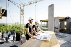 Workers with drawings at the construction site. Two workers in black t-shirts and protective harhats working with drawings at the construction site outdoors royalty free stock photos