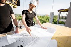 Workers with drawings at the construction site. Two workers in black t-shirts and protective harhats working with drawings at the construction site outdoors stock images