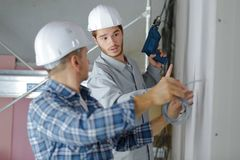 Workers drill wall in house to put cable. Workers drill a wall in house to put a cable Royalty Free Stock Photos