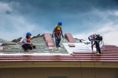 Workers are drilling roof tiles with a drill. Stock Photo