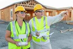 Workers with Drone Quadcopter Inspecting Photographs on Controller royalty free stock image
