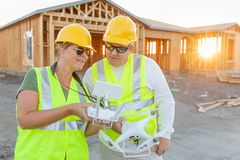 Workers with Drone Quadcopter Inspecting Photographs on Controller royalty free stock photography
