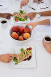 Workers eating healthy lunch during meeting Stock Image