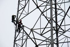 Workers on the energy pole. A grid of newly installed energy pole with employees. Autumn season Stock Photo