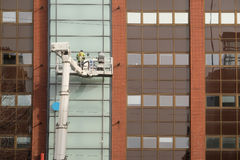 Workers is engaged in restoration of the modern multi-storey building Royalty Free Stock Photography