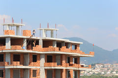 Workers erect balconies from brick in new building. At top floor royalty free stock photography