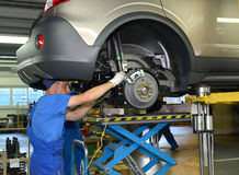 Workers establish depreciation racks on the car. Assembly convey Stock Photo