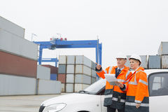 Workers examining cargo in shipping yard Royalty Free Stock Photo