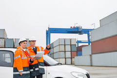 Workers examining cargo in shipping yard Royalty Free Stock Images