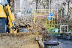 Workers excavate the pit with an excavator. Road repair. Pipeline failure stock photography