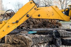 Workers excavate the pit with an excavator. Road repair. Pipeline failure royalty free stock images