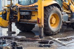 Workers excavate the pit with an excavator. Road repair. Pipeline failure royalty free stock photo