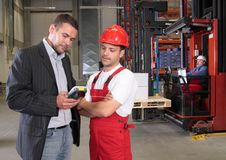 Workers in factory. Boss talking to worker in uniform in factory royalty free stock photography