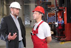 Workers in factory. Boss talking to worker in uniform in factory royalty free stock image