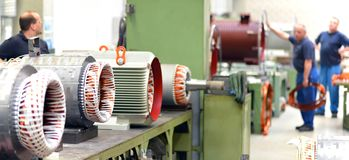 Workers in a factory assemble electric motors. Closeup photo stock image