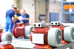 Workers in a factory assemble electric motors. Closeup photo in background workers royalty free stock images