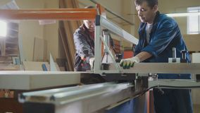 Workers at factory are cutting wooden fragment on electric saw at furniture industry Royalty Free Stock Image