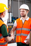 Workers in factory. In factory male engineer and workman shake hands stock images