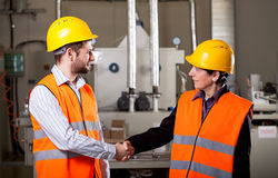 Workers in factory shake hands Stock Photos