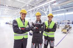 Workers in factory. Team of three workers in uniform standing at background of CNC factory Stock Photography