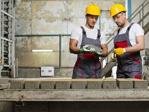 Workers on a factory. Worker and foreman in a safety hats performing quality check on a factory royalty free stock image