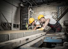 Workers on a factory. Worker and foreman in a safety hats performing quality check on a factory stock photo
