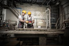 Workers on a factory. Worker and foreman in a safety hats performing quality check on a factory stock images