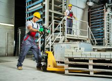 Workers on a factory. Young worker moving paving stones with pallet truck on a factory stock photos