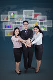 Workers and financial graph joining hands Stock Photo