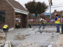 Workers finish cement at bus stop royalty free stock images
