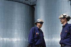 Workers and fuel storage tanks Stock Photo