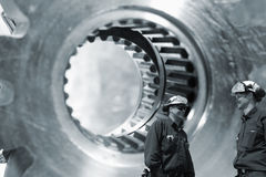 Workers with giant gears and cogwheels axles Stock Images